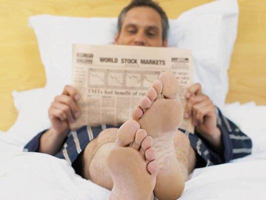 Hombre en la cama leyendo el periódico
